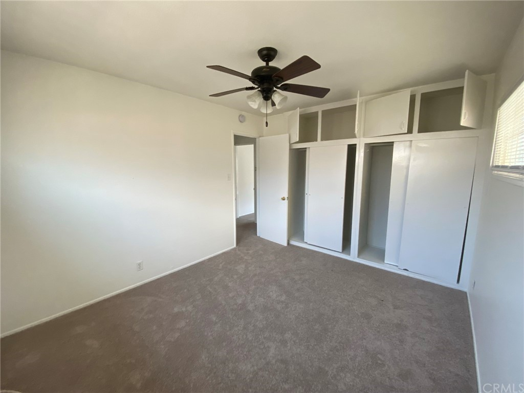 Bedroom A with double closet, double upper storage and ceiling fan.