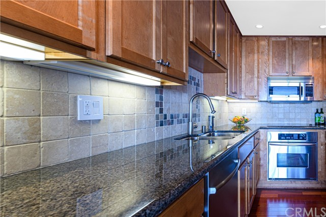 View of Kitchen with built-in appliances, granite counter and stone backsplash