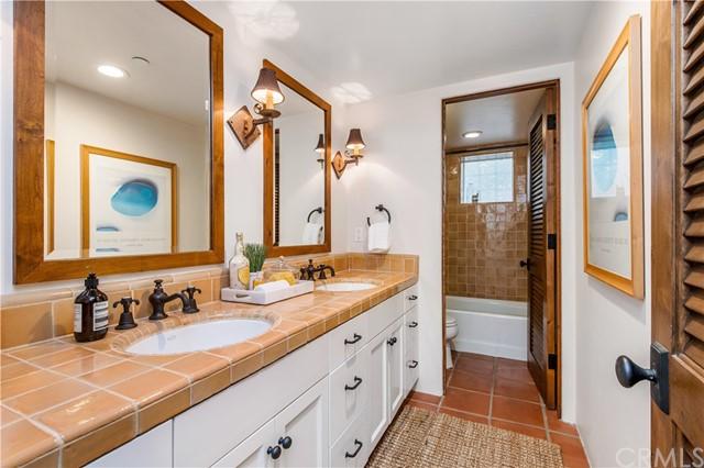 Full bathroom located on the lower level features dual sinks and private bathing experience.