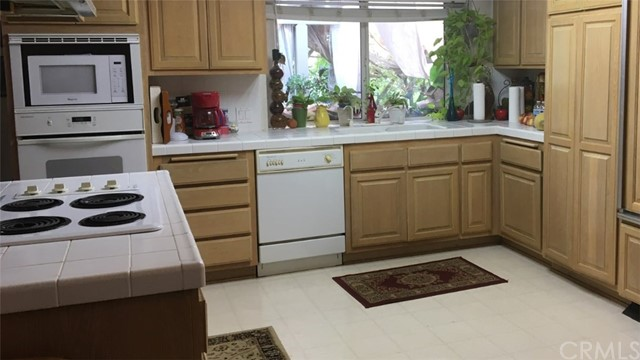 Kitchen with Microwave, Oven, Electric Stove, Dishwasher and Built in Refrigerator on the right