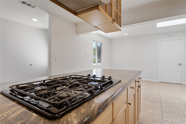 Built in stove in kitchen and family room in the background.
