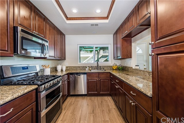 Remodeled kitchen with warm dark wood cabinets and granite surfaces!