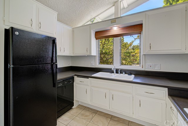 Another view of the kitchen. Large windows bring in ample light. Lots of cabinet storage.