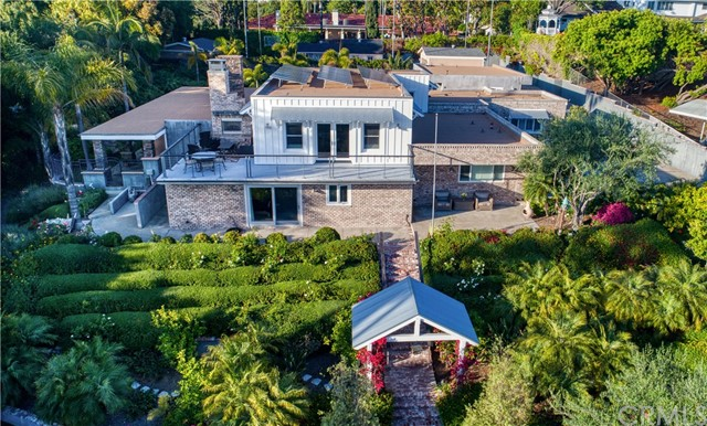 Over $1.4M spent to create this turn-key, private gated estate, with elevations that capture panoramic views of Orange County. This superb, solar-powered custom home, offers luxurious resort-style living on a secluded, nearly one-acre lot. Featuring 5 bedrooms, 5.5 baths & 5,481 sf, the well-appointed & open floor plan is highlighted by high-end, architecturally pleasing finishes. Multiple windows & patio doors create a seamless transition indoors & outdoors. Impeccable craftsmanship with French farmhouse influences; pride of ownership is apparent upon arrival. The dramatic great room with soaring ceilings is ideal for entertaining while the gourmet, eat-in kitchen is a chef's envy with high-quality appliances & finished materials; it opens to a sitting & formal dining room, warmed by a fireplace. Mostly one-story living with only a bonus room upstairs with access to a viewing deck & exterior fireplace to enjoy beautiful sunsets. Custom barn doors on the main level open to a media room with a fireplace & built-ins. Outside rests a permitted 850 sf guesthouse with a living room, bathroom, bedroom & kitchen. The trophy landscaped grounds include several covered patios, an activity pool/spa, built-in bbq & bar, firepit, floodlit sports court, 2 finished garages for 5 cars, a storage barn & workshop. With award-winning schools, this vast property raises the bar from any other home available in the area today. Welcome home to your own sanctuary & entertainer's paradise!