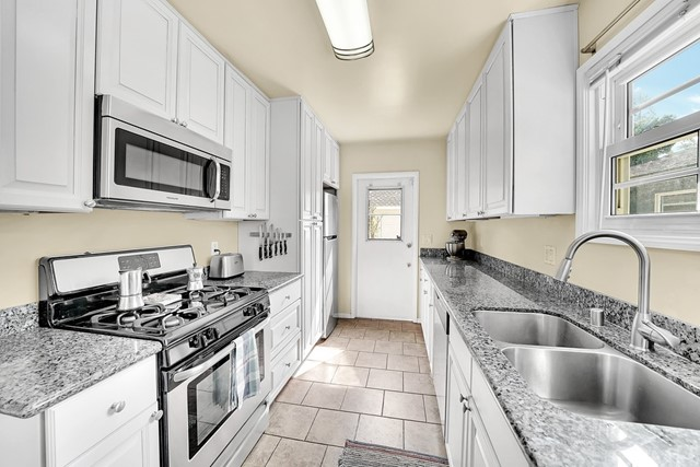 nicely appointment galley kitchen with outdoor yard access