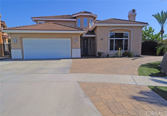 TAKE THE REINS of this newer Las Riendas Court custom built home in an established area of Fullerton with No Mello-Roos or HOA dues, in a quiet cul-de-sac. Tumbled pavers lead to the custom designed mahogany entry door and wrap around to the large wrought iron double gate for RV access. You will be greeted by a light and bright open foyer with a 2 story ceiling and plenty of natural light. The custom colors and rounded corners accent the interior architecture. The Formal Dining Room has wainscoting, chair rails, and crown molding. Gourmet Kitchen has an over sized granite slab kitchen island. Imported Italian Greenwich porcelain tile flooring throughout kitchen and nook. Kitchen is open to the spacious Family Room featuring a fireplace, stacked stone seating. Downstairs also features one and a half bathrooms with matching counter tops, cabinet and flooring. Large bedroom and access to laundry and three car tandem garage. Garage has a dry walled interior complete with window for future 5th bedroom conversion. Upstairs are the spacious Loft and Tech Center. There are two additional spacious bedrooms and bathroom. Master Ensuite Bedroom features, room for additional seating. Master Bathroom features over sized large soaking tub, separate shower and private toilet area. Additional room for seating or vanity and spacious walk-in closet with built-ins and overhead storage. Gas heated automated pool and jacuzzi features night-time lighting. Side yard has paved basketball half court.