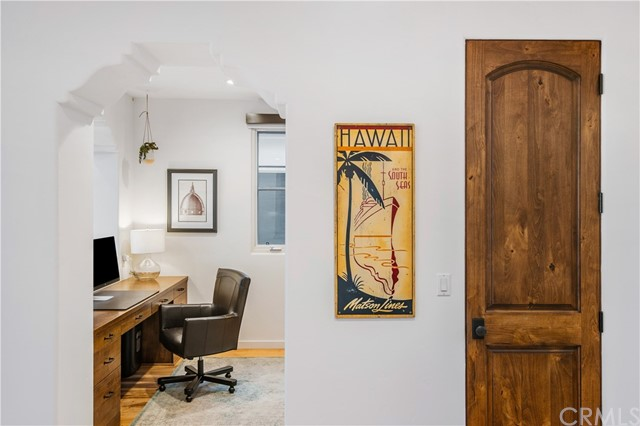 Just off the kitchen sits an open office which looks straight to the Pacific Ocean and features a built-in desk and cabinetry.