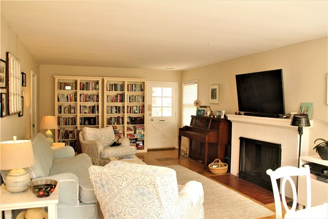 Original oak hardwood floors and simple brick fireplace in living room. Front door is facing North. Bookshelves are not built-in.