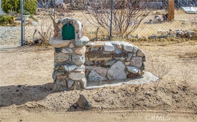 Stonework address marker and mailbox.