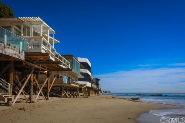 This 2BR, 2BA Malibu house has a private stretch of pristine beach! Floor to ceiling windows offer breathtaking ocean views, and you're only a short walk from shops and cafes. A small patio with benches and plants greets you as you step up to the home. From the front door, you're surrounded by breathtaking views of the ocean, courtesy of the floor-to-ceiling windows in the living room. There's wooden flooring, and a gas fireplace that crackles with warmth once the sun has gone down. A large flat-screen TV offers a chance to curl up with your favorite show. More ocean views wrap around the dining room. The adjoining modern kitchen has stainless steel appliances and plenty of counter-top equipment. In the master bedroom, a king bed sits by a rocking chair. The en-suite bathroom has a shower/tub combo. Bedroom 2 has a queen bed and lots of books to make the evening fly by. The en-suite bathroom features a step-in shower with a 2nd access door to the side boardwalk—follow your nose and let the ocean air lead you straight to the beach! A long wooden deck stretches out in front of the home, where there's ocean views aplenty, outdoor seating, plus an umbrella for shade. Perched right on the golden sands of Malibu, you'd be forgiven for not wanting to be anywhere but home! This gorgeous beachfront home offers you the chance to enjoy your own private slice of sun-soaked paradise along with them!
