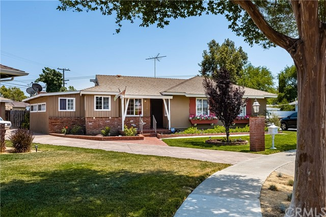 Absolutely Brilliant and Beautifully Updated Home in Anaheim! Situated on an oversized 8,925 sqft  lot and located in a quiet community, this 3BR/1.5BA, 1,493 sqft abode welcomes with cozy covered front porch, stately exterior brick detailing, and tidy landscaping. Originally built in 1955, the meticulously maintained home has been superbly updated over the years. Enter through the front door with colorful glass inlays to find wood floors, neutral scheme, bright white trim, and an openly flowing traditional floorplan. Imagine cooking healthful meals in the modern semi-open concept kitchen featuring a gas range, ample white cabinetry, solid surface countertops, white tile backsplash, dishwasher, and an adjoining laundry area. Expansively sized and entertainment-ready, the living room may accommodate large furniture and includes a fireplace and a door to the outdoor space. Created for huge parties and summertime fun, the fully enclosed backyard features a fenced-in swimming pool, huge covered patio, and a sprawling green-space. The main bedroom has a wide closet and an attached ½ bathroom. Two additional bedrooms are generously sized with dedicated closets, while the full bathroom has a shower/tub combo with retro tile-work and a long vanity. Other features: detached 2-car garage, family room, linen cabinet, near shops, dining, and schools, and so much more! Call now for your showing!