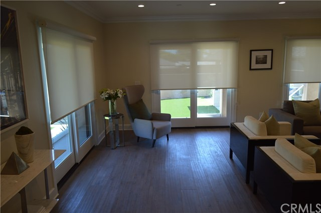 Family room with a view towards the backyards after installation of rollup shades over each sliding door.