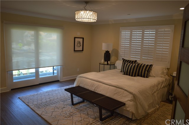 Master bedroom after installation of rolldown shades over the sliding door and plantation shutters on the window.