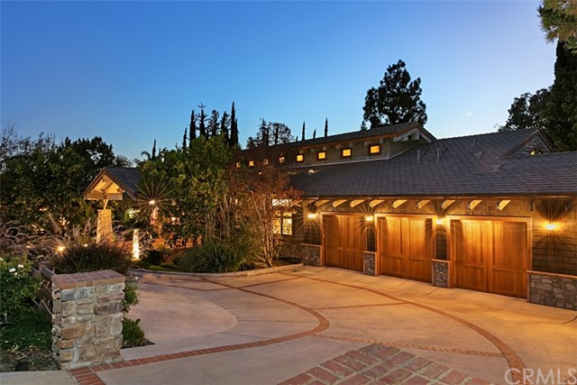 Designed and inspired by Yosemite National Park's luxurious Ahwahnee Hotel, this stunning single-story contemporary craftsman features soaring vaulted cathedral ceilings with exposed beams and clerestory windows. An expansive Kitchen, just off of the Great Room, includes an oversized island, marble countertops, double sink/prep-sink and a Butler's Pantry. Top-of-the-line stainless steel appliances include a Viking convection oven/stove, built-in refrigerator, 2-dishwashers and microwave. There are 3 gas-burning stone fireplaces that serve the formal Living Room, Dining Room and outdoor patio. Built-in home audio system covers the main rooms, Guest Quarters and outdoor patio areas. 4 of the 5 bedrooms enjoy orchard views. The Guest Quarters includes a 3/4 bath, walk-in closets and stairs leading up to the sky-lit retreat. The wrap-around stone patio with outdoor fireplace and entertainment areas are all accessible from the main areas of the home. Mature lush professional landscaping surrounds the saltwater pool which can be seen from all of the main rooms, including the Master Retreat. Inside Laundry Room includes a sink and plenty of storage. Exquisite wood casement windows and Venetian plaster walls throughout, including the garage! The attached 3-car garage includes an Electric Vehicle charging port for 2 automobiles. Other energy saving, hi-tech/smart home amenities includes seller-owned solar roofing panels, a Ring home security system and two Nest learning thermostats.