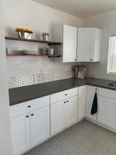 Quartz kitchen countertops with tile backsplash.