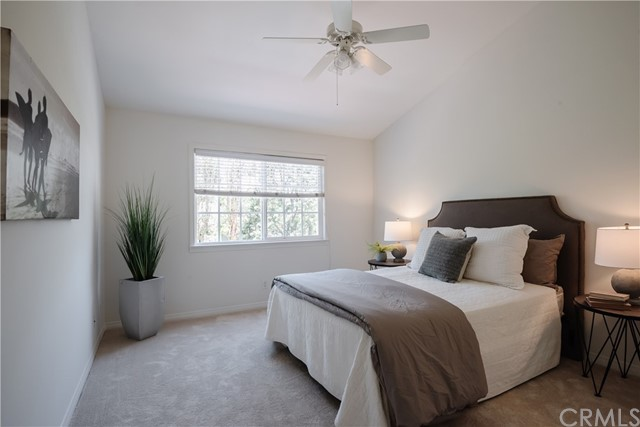 A secondary vaulted ceiling Bedroom with ceiling fan.