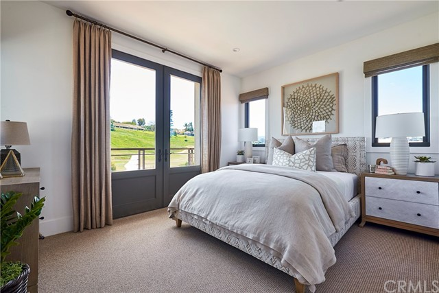 Upstairs bedroom suite with balcony & French doors, near bonus room. Model home shown.
