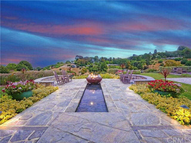 an outdoor firepit with beautiful water feature