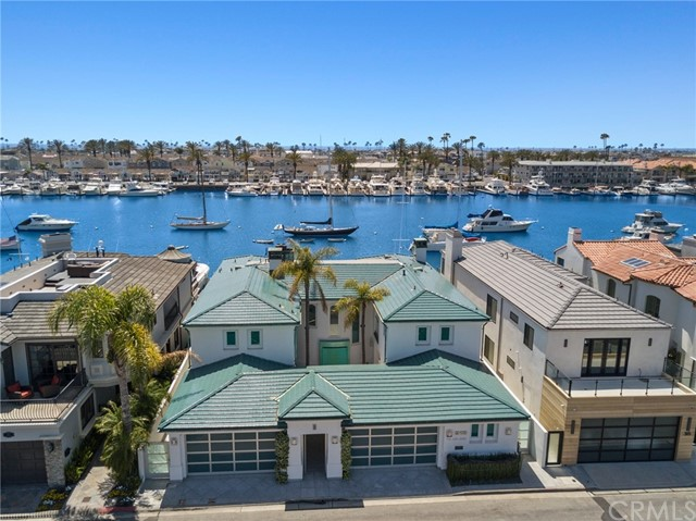 """Are you in search of the """"uber cool"""" and """"ultimate fun"""" 12-month unfurnished lease? This Lido Isle bayfront home, on an extraordinarily large 60' double lot, with a boat dock for two large yachts, and featuring spectacular Newport Harbor views is in move-in ready condition. The 4,600 square foot home with perfect southwestern exposure, features a large living room with a double-sided fireplace, formal dining room, media area with a built-in bar, keg refrigerator, ice machines, and a high-definition television, and a big island kitchen with granite countertops, professional grade stainless steel appliances including a coffee maker, six burner cooktop, double oven, trash compactor, wine refrigerator, Subzero Refrigerator, icemaker, dishwasher and so much more. In addition, the lower level has a large laundry area with two sets of washers and dryers, and a three-car attached garage. The lower level is highlighted by the huge bayfront patio with a built-in entertainment center, sit down countertop bar, BBQ, refrigerator, Jacuzzi and more. The upstairs of the home features a huge bayside master suite with an office or retreat, fireplace, private balcony, stunning bath with a jacuzzi, sauna and walk-in closet, and a big guest suite with a marble bath and vanity. The big dock can accommodate two large boats, one potentially to 70' and a side-tie.  Lido Isle is the ultimate lifestyle community with its private beach club, sailing, tennis courts, parks and activities for all ages. This property is within an easy walk of the new Lido Village with its upscale shops, restaurants, and nightlife."""