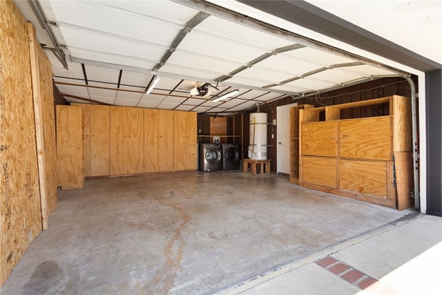 Garage picture with custom made cabinets. Washer/Dryer in the background
