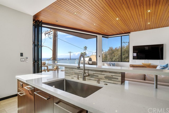 Folding doors open onto an ocean view deck; view from the kitchen