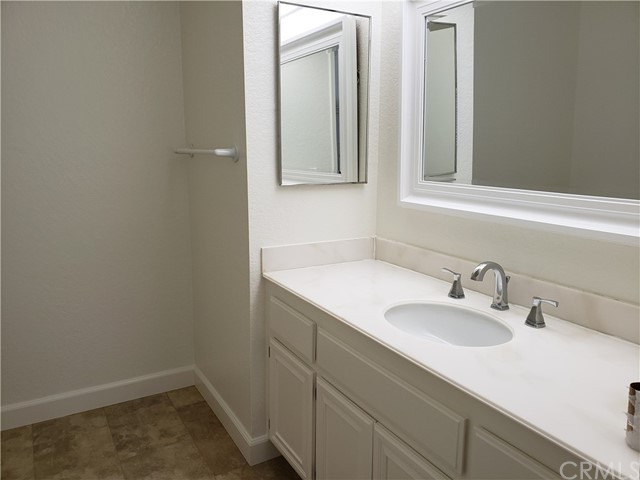 One of the master bathrooms with a newer framed mirror