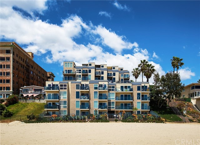Beachfront condo with a magnificent ocean view.  Beautifully appointed end unit with views up and down Long Beach's coastline. You'll be enamored upon entry, greeted by a view out a large picture window. Gleaming wood flooring and complementary paint color create a warm feel throughout the home.  The recessed lighting, along with the stream of natural light, makes for a perfect atmosphere, day or night. The kitchen has been elegantly remodeled with rich colored custom cabinetry with metal frame glass doors, quartz counters, glass tile back splash, stainless farm house sink and Kitchen Aid appliances.  The equally exquisite bathroom has convenient dual vanities, large shower with stylish tile and frameless enclosure. Plentiful closet space highlights the spacious bedroom which has direct access to the bathroom.  Parking won't be a problem with tandem parking for 2 cars. Enjoy and take in the views from the rooftop deck or take a dip in the sparkling pool. Easy access to the beach and within walking distance to wonderful restaurants, entertainment and shopping.  You'll feel like you're always on vacation!
