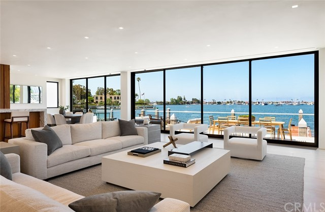 Just completed, this bay front home occupies the most sought-after location on Newport Harbor. Set behind the manned gates of Linda Isle, this 5,500 square foot residence of contemporary design is meticulously finished with the finest of interior appointments. The result is a home that is uncommonly spacious, light, and livable. Walls of floor-to-ceiling glass on both levels capture the very best uninterrupted westerly views over the main turning basin - considered to be the best on the harbor. The primary suite spans the width of the property on the second floor and features astounding views. It includes two baths and dressing areas, as well as a sitting room. Other features of the home include a two-story gallery entry, a media room, two kitchens (main and catering), a commercial elevator, and a private dock for a yacht in excess of eighty feet. This is a nearly perfect home, in a perfect location. More information is available upon request.