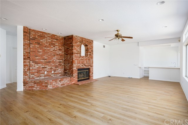 A large family room with a wet bar at the end of the room and the natural light coming in. A natural gas brick fireplace.