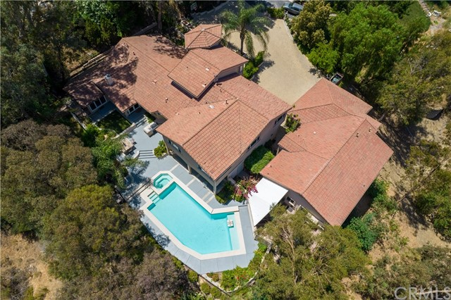 Nestled among the trees is this custom crafted estate comprised of a spacious Main House and a 1,200 sq ft Guest House with a private 800 sq foot apartment or maids' quarters. With a view of the hills, this property is positioned on a private and secluded 37,500 square foot lot in the prestigious Mohler Loop neighborhood of Anaheim Hills. This compound is ideal for multigenerational living. Using fine finishes and attention to detail, the main house was extensively remodeled in 2011 and consists of 4600 square feet of living space, custom double entry doors and 3 car garage. Enter through double doors with custom wrought iron inlays, notice private dining to the left and family room to the right, with custom bar area in the center with adjoining guest seating. Formal dining room is capable of seating multiple guests for private dinner parties and is just steps from the upgraded kitchen boasting dramatic dark wood like flooring, granite counters and stainless appliances including dual ovens and 6 burner cooktop. This tri-level home has 6 beds, 6 baths, inside laundry and poolside view of the hills. Offering a desirable first floor master suite with retreat and dual sliders, one to a private observation deck overlooking the hills, and to the sparkling saltwater pool. The main house is completed with a second master and inside laundry on the upper level. The guest house on the lot was constructed in 2013 and has a courtyard entry with gated garden and path to the pool deck. Enter through beautiful hand crafted walnut doors to an inviting interior with Brazilian walnut floors, large kitchen with GE Monogram appliances and concrete counter tops. The main level consists of a family room, large bar with seating area, private maids' quarters with dedicated entrance, private deck area, kitchenette, and indoor lap pool. Great opportunity for investors: the Main House could potentially command $8,200 and the Guest House $3,500-4,000 per month in rent. Notable features: Built o