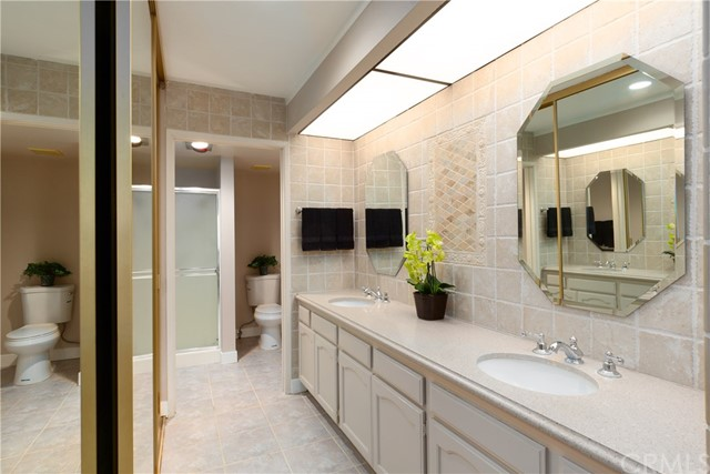 The dressing area has beautiful silestone counters and ceramic tile backsplash with medallion.