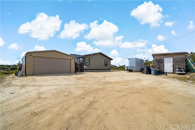 Front parking area w garage to left and storage shed at right.