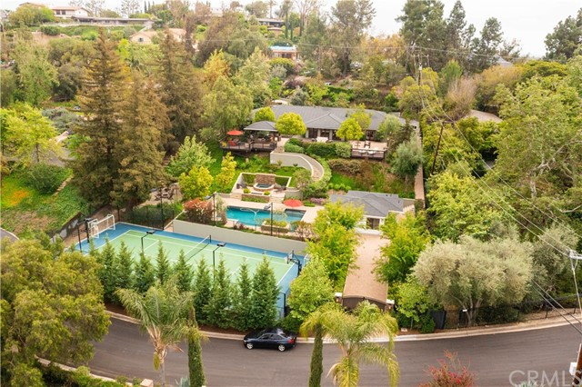 RESORT LIKE ESTATE - This serene estate is located on an exclusive street in the rolling hills of North Tustin and is one of the finest estates available on the market today. Resting on 42,750 square feet (.98 of an acre) of land, this home offers the ultimate in seclusion with a resort-like feel and mature landscaping. Featuring a total of 3,992 square feet of living space, the main house encompasses 5 bedrooms with 4 baths plus a separate guest house by the pool. The open concept floorplan provides a seamless transition for indoor and outdoor living while an abundance of natural light permeates every room. The entertainer's kitchen boasts a massive island with seating for 4, white shaker cabinets, Carrara marble counters, and Fisher & Paykel appliances. The kitchen opens to a great room and dining room surrounded by glass windows and french doors offering picturesque views of the hills near Peter's Canyon. There is easy access off the main house to the outdoor kitchen, serene pool with a Baja shelf, multiple seating areas, firepit, and a multi-sports court. The guest house has an open floor plan and kitchen, all serviced with its own bathroom. In addition, the home has 2 separate driveways giving access from both Rangeview Drive and Cowan Heights Drive and can accommodate boat or RV parking with the potential for utility hook-ups. Top Tustin schools complete this exceptional property.