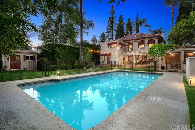 Built in 1925 by W.J. Nethery for the Gunnerson family, this 1925 Mediterranian Revival is on the market for the first time in almost 3 decades. This extraordinary residence is located on sought after, rarely available, Chapman Place, the soul of the Historic Wood Streets neighborhood and in the heart of the city of Arts and Innovation, Riverside, CA. This stately vintage home has been brilliantly cared for, meticulously maintained, & thoughtfully upgraded by the current owners. The majestic palms, manicured boxwoods, & white rose complement the architecture, wrought iron, & beveled glass door. The entry is bookended by 2 sets of glass pocket doors, original fixtures, & a wood staircase w/ wrought iron provides for a dramatic welcome. The living room contains original light fixtures, wood windows, & fireplace with wood mantle. The adjoining den looks towards the back yard & provides access to the patio/pool. The dining room is filled with natural light from 4 windows & is the perfect setting to host intimate cocktail parties or a large Thanksgiving meal with family & friends.  The kitchen is charming w/ a farmhouse sink, white cabinets, cobalt subway tiled counters, and 4x4 earth-colored tile flooring. Two sets of stairs lead to the second level where the primary bedroom along with 3 additional bedrooms and two separate bathrooms are located. The primar