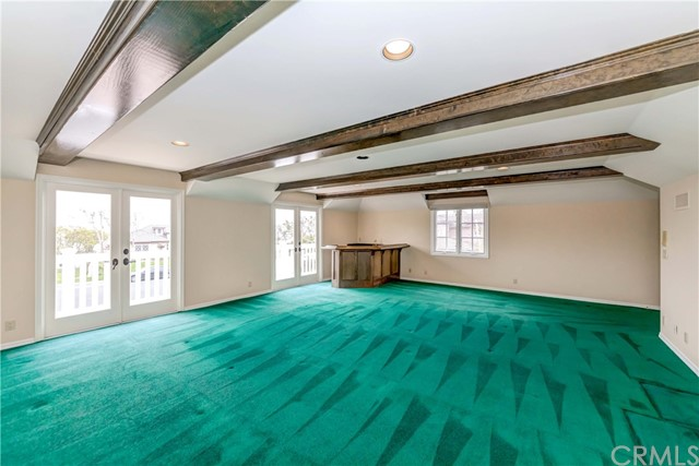 Bonus/Game room with wet bar at the corner, fireplace, and french-door to balony