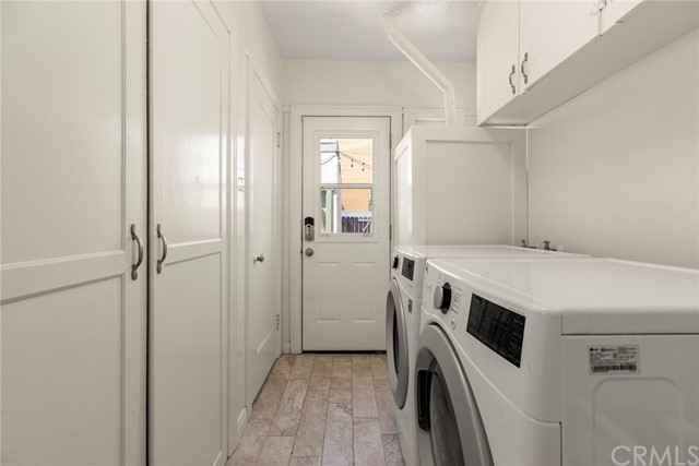 Directly off the kitchen is the light and bright laundry area...(Note all the additional storage above and across from the washer & dryer)