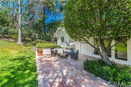 Enchanting estate, filled with warmth. Beautiful mature trees adorn the entry.