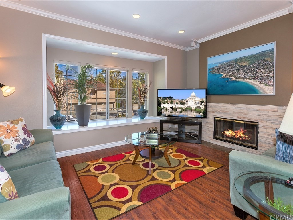 Upgraded Carriage style end unit with abundant natural light and privacy.  Enter unit from lower level front door or direct garage access.   The entry level has a full size laundry room with washer and dryer.  The main living area of the home is an upper single level and has been tastefully updated with engineered wood floors, crown & base mouldings, indirect lighting throughout most rooms, surround sound system, cozy wood burning fireplace with stone surround, patio doors to the enclosed (not covered) patio deck and lots of natural light streaming through.  The kitchen has stainless appliances, rich granite countertops, tile backsplash and counter bar adjacent to the dining room area.  The bathtub/shower has updated tile and is a jack and jill bath with newer vanities, mirrors & lighting.  Master bedroom has a walkin closet.  The heating/air conditioning & water heater is newer.  Very spacious open floor plan.  Good guest parking right in the CDS, easy access to two shopping centers with grocery stores & restaurants.  the area offers parks, biking and hiking trails and golf course close by.  Short distance to world renown resorts, beaches, Dana Point Harbor & Laguna Beach.  This is a wonderful move-in ready home with an ideal location. HOA fee covers trash & basic cable.  Property may be purchased fully furnished.