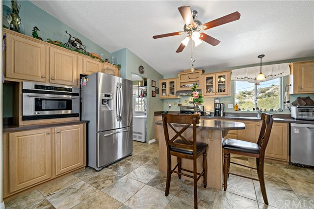 Kitchen w stainless steel refrigerator (included in sale) and built-in microwave w hillside view thru window at sink.