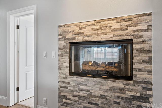 Romantic 2 sided gas fireplace decorated with colorful brick