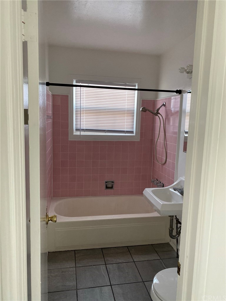 Full bathroom with tub and shower. This photo is a vacant unit on the left that shows the floor plan of the units for sale.
