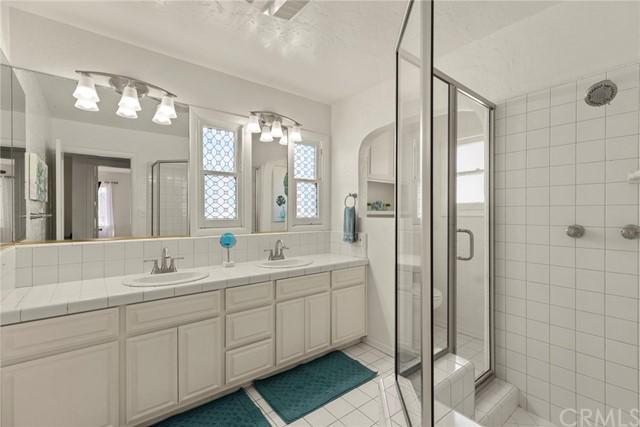 Upstairs bathroom features beautiful windows, dual sinks, a vanity with plenty of cabinet storage and a large shower....