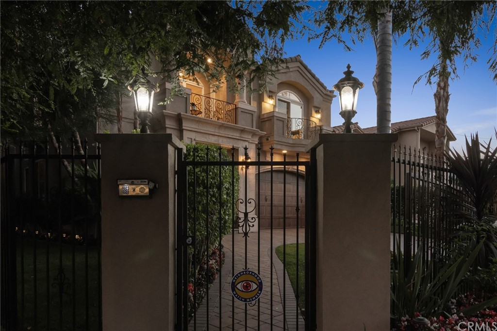 Twilight photo of the front of the house with security gate.