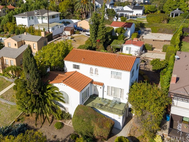 Perched high above street level overlooking the lush greenery of Averill Park is this 1930's Spanish stucco estate awaiting it's next owner to return it to it's original glory. This San Pedro Classic is nestled among other Estate-type properties in one of the most prestigous of San Pedro neighborhoods. The quality of construction is evident throughout the home with the hand-troweled plaster walls, natural wood built-ins and cabinetry, arched doorways and wrought iron railings. Home is carpeted throughout but there appear to be beautiful hardwood floors in just about every room. Lower level features the impressive main living room/parlor with fireplace, sunlit formal dining room, spacious kitchen with breakfast area, one bedroom, a 3/4 bath and charming laundry area. Upper level offers 3 more bedrooms including the master and another full bath.  A nice surprise is the peek of harbor views that can be enjoyed from the upper level bedrooms. Finished basement area with direct access from interior of home adds another approximately 500 sq ft of living space and has it's own entrance. Massive rear yard offers over 8500 sq ft (70 x 122) of usuable land that could be developed to include another home (ADU), swimming pool, RV parking, more garages, gardens or whatever you heart desires. A rare opportunity to own one of the true Estate-type properties in San Pedro. The possibilities are endless.