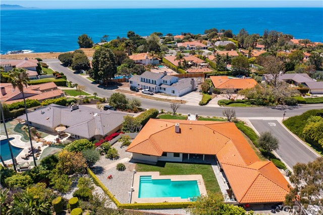 Perfectly positioned on an impressive, estate-sized elevated corner lot with views of the ocean and Catalina Island, this single level pool home is the one you've been waiting for.  It's located on a quiet street among the most prestigious homes in Lower Lunada Bay, three doors to the bluff, yet within walking distance to all three award-winning schools. Upon entry, you'll experience expansive living and dining areas, a pleasant ocean cross-breeze and an open sight line to the large, flat yard that features a pool, full outdoor kitchen and an indoor/outdoor pool cabana (which has been used over the years as an office and workout room).  The overall layout is conducive to entertaining in a relaxed style, with ocean views from the main living spaces and even from the pool deck!  Beyond the pool, grass lawn, fruit trees, and three car garage, there's additional space for a sport court or storage of your ocean gear and jet skis. Interior updates include lifeproof flooring, a pool-view kitchen with pass-through window, freshly painted cabinets, granite counters and stainless steel appliances, plus recently remodeled bathrooms and newer windows.  The oversized primary bedroom enjoys ocean and sunset views, a walk-in closet and an en-suite bath with dual vanity.  Life is peaceful here, where the sounds of the ocean, birds and the R10 buoy provide a backdrop far-removed from the city. Offered for sale for the first time in 50 years, this is a treasured family legacy property.