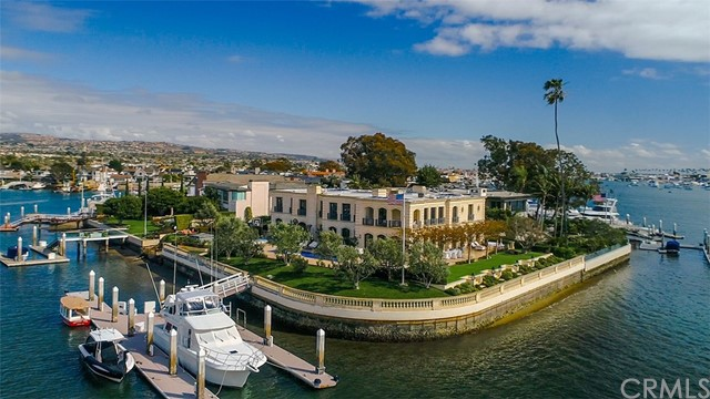 A landmark promontory location defining the spirit of the Newport Harbor – 18 Harbor Island. Here classic architectural structure meets a forward-thinking design aesthetic, creating a one-of-a-kind waterfront treasure with over 300 feet of bay frontage. With clean lines, open space and purity of form the re-mastered residence with a total building size of approximately 16,000 square feet lives graciously with large-scale rooms and a panorama of sublime water views. Beautifully and tastefully appointed tA landmark promontory location defining the spirit of the Newport Harbor – 18 Harbor Island. Here classic architectural structure meets a forward-thinking design aesthetic, creating a one-of-a-kind waterfront treasure with over 300 feet of bay frontage. With clean lines, open space and purity of form the re-mastered residence with a total building size of approximately 16,000 square feet lives graciously with large-scale rooms and a panorama of sublime water views. Beautifully and tastefully appointed the exquisite finishes and custom refinements are flawlessly employed. Abundant natural light cascades throughout the formal and informal spaces, illuminating the myriad bespoke details of this transformed neoclassic home. The grand-scale of the interior balances seamlessly with multiple exterior limestone terraces, flowing gardens, and a magnificent pool surrounded by the glistening waterfront and captivating, lively views of the harbor turning basin. A newly reconstructed yacht accommodation for a craft in excess of 120 feet, as well as additional boats and water toys is sited along the western portion of the estate grounds. Rich with history, the guard gated Harbor Island enclave is perhaps the most coveted address along the waterfront in Southern California. Poised at the island's tip and transcending all others, the space and views afforded by this distinguished residence cannot be replicated.
