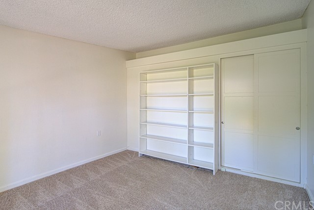 Master bedroom has shelving and closet.