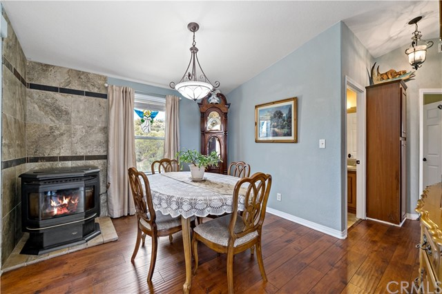 Formal dining room w pellet stove at left and hillside view thru window.