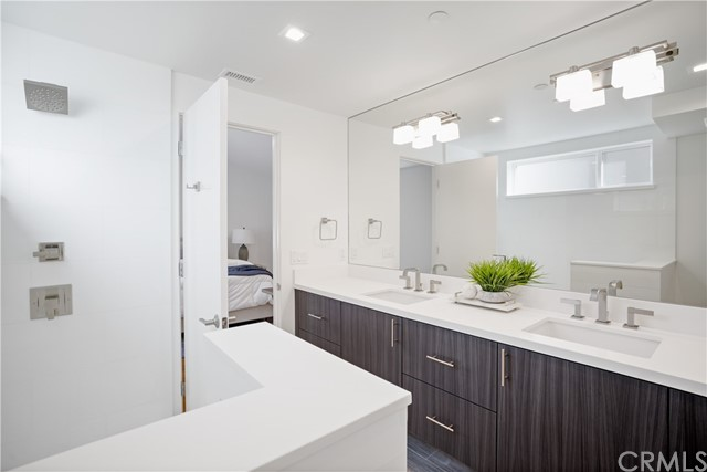 Master bath with floating cabinets, quartz countertop, counter-to-ceiling mirror