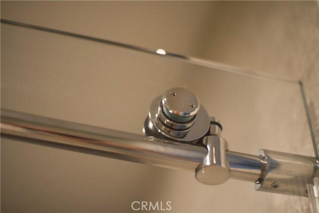 Detail of frameless sliding glass shower door-Master ensuite